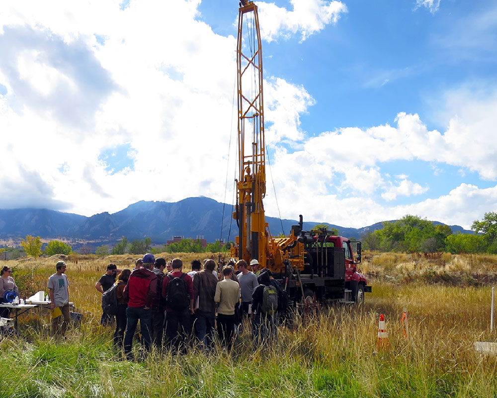 drill rig demonstration outside in tall grass field